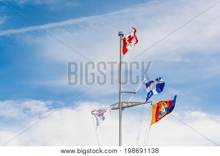 Portneuf Canada - May 29 2017: Many flags on pier isolated against sky on Chemin du Roy by Saint Lawrence river