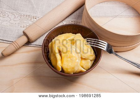 Fresh Boiled Varenyky Or Dumpling With Cottage Cheese Or Curd In Clay Bowl And Metal Fork On Wooden