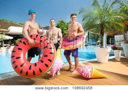 Concept of a summer party and holiday. Smiling group of friends with inflatable swim rings in front of a swimming pool. Young happy guys having fun and enjoying summertime in a aquapark.