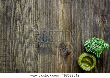 Broccoli puree for baby on dark wooden table background top view.