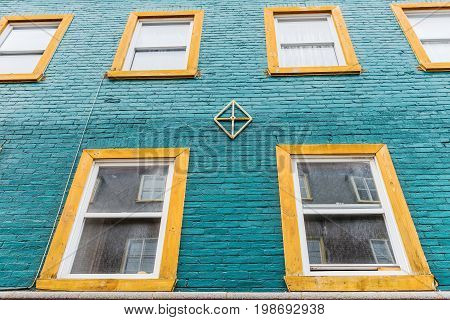 Blue Brick Wall And Yellow Decorated Windows Architecture In Colorful European City
