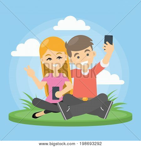 Couple take selfie. Smiling man and woman sit on the field and take selfie on smartphone.