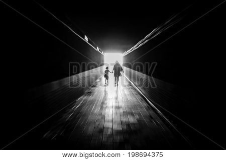 People go through the tunnel. Silhouettes. Black and white. Zoom effect and the radial blur.