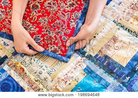 tradition, crafts, needlework. caucasian woman holds rag by hands in order to demonstrate the quality of needlework and beaty of ornament consist of traditional slav patterns