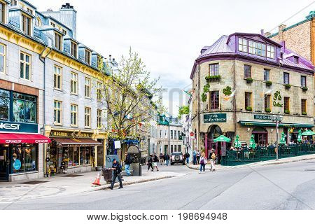 Quebec City Canada - May 29 2017: Old town street with people walking by Pub St Patrick restaurant entrance bar crossing road