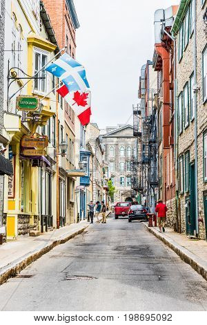 Quebec City Canada - May 29 2017: Old town street Rue Garneau with flags and people walking