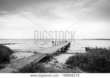 Pier on a Scandinavian beach in black and white with cold dark water on cloudy sky