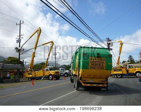 OAHU HAWAII - OCTOBER 17 2012: Honolulu Disposal Service Truck Blocks Road as HECO trucks and workers do repairs to power-lines above street in Waimanalo Hawaii.