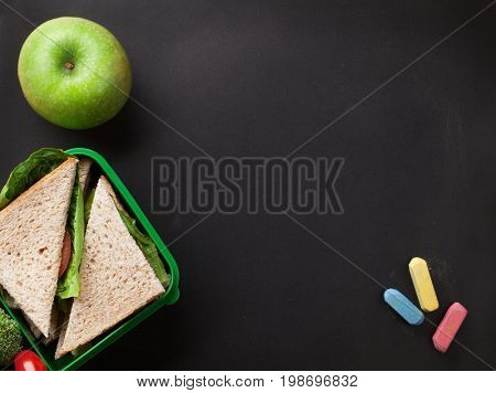 Lunch box with sandwich and vegetables. Kids take away food box. Top view on blackboard with space for your text