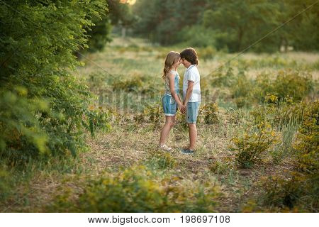 Little girl and boy are standing in forest holding hands and looking at each other. First love.