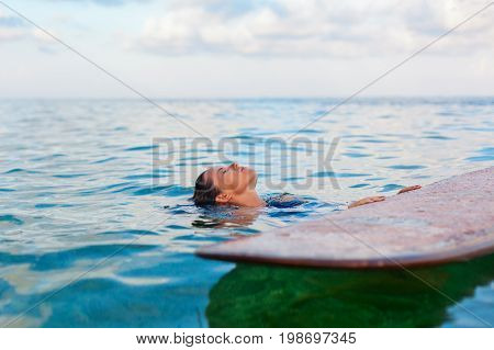 Happy woman in have fun before surfing. Surfer girl hold surf board look at sunset sky. People in sport adventure camp extreme water activity on family summer beach vacation. Watersport background
