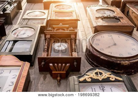 Various of vintage wall clocks hanging on old wood wall.
