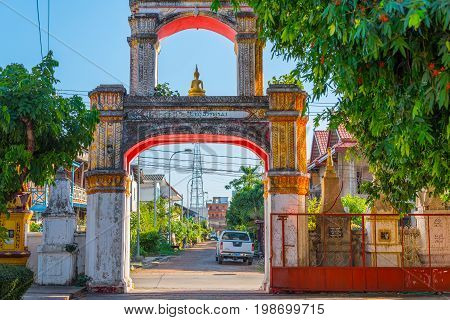 Savannakhet, Laos - February 2, 2017: Gates of an old temple with a small golden Buddha on the top of the gates.