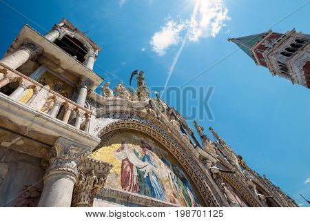 Low angle view of the Basilica di San Marco (Saint Mark`s Basilica) and Campanile in the Piazza San Marco in Venice, Italy. This is the main square of Venice.