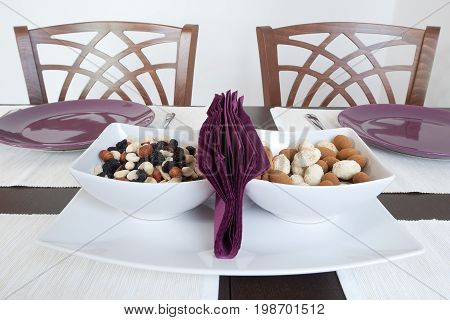 Laid table, purple plates and bowls with a nuts