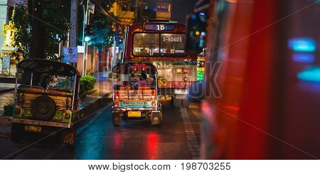 Bangkok, Thailand - February 18, 2017: Night ride a on public bus with tuk-tuks and a public bus view. Night scene of Bangkok life