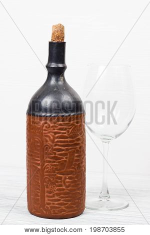 Black bottle of wine and wneglass on the background of the canvas