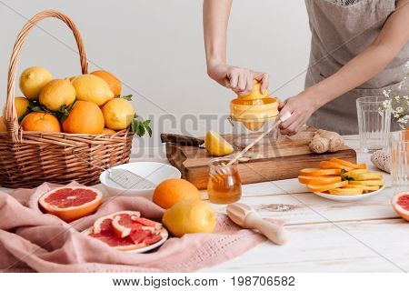 Cropped picture of woman standing indoors and squeezes out juice of a citruses.