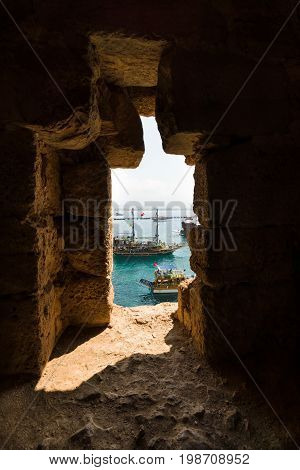 ALANYA TURKEY - JULY 04 2015: Traditional entertainment resort of Alanya. Sailing aka pirate ships around the fortress of Alanya. View from the medieval shipyard (Tersane) of the Alanya Castle.
