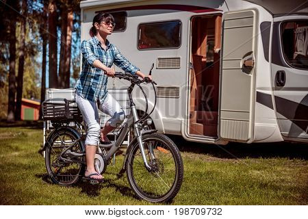 Woman on electric bike resting at the campsite. Family vacation travel, holiday trip in motorhome, Caravan car Vacation.