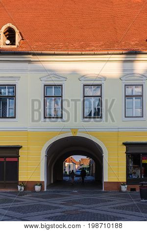 Facade of ancient house with archway and orange tiled roof on the street in a Sibiu city Romania.