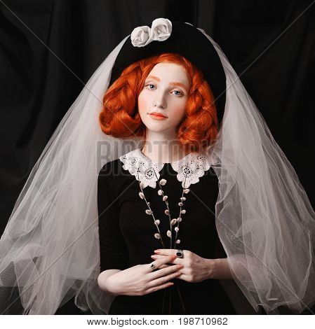 Young vintage girl. Redhead victorian vintage girl with long braids with an unusual appearance in a black dress with a cap and veil on her head. Lovely vintage girl with pale skin and rings with stones on a black background. Nice vintage girl. Pretty vint