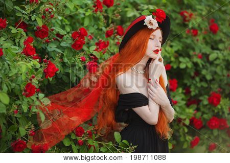 Redhead woman with very long hair with unusual appearance in black dress against background of red roses. Attractive unusual  girl with pale skin and bright unusual  appearance with black hat and red veil. Art photo. Unusual  model. Unusual  look