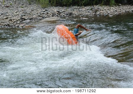 Inner tube float wipe out on white water rapid at Clear Creek White Water Park in Golden, Colorado
