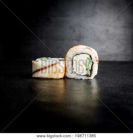 Sushi rolls with fish on a black background. Japanese food