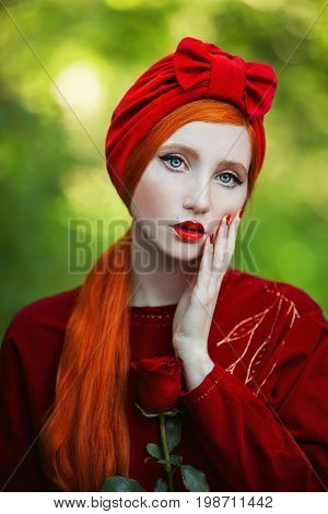 Bright retro girl with pale skin and long red hair a red dress and a turban on a summer background. Bright girl in retro turban with red nails and a rose in her hand. Red turban. Bright retro turban in girl head. Bright background. Bright woman