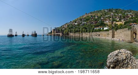 Shipyard (Tersane) and the ruins of a medieval fortress (Alanya Castle) on the mountainside. Panoramic view. Alanya. Turkey.