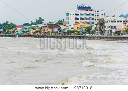 PRACHUAP KHIRI KHAN, THAILAND - MARCH 28, 2017: Stormy cloudy weather, waves beat against the seafront of the city. Storm comes on the Gulf of Thailand.