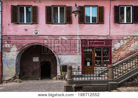 Detail of facade with wooden arch doors and windows in neglected ancient house in Sibiu city Romania.
