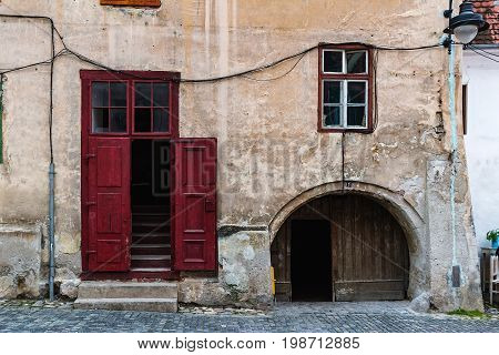 Detail of facade with wooden red doors and window in neglected ancient house in Sibiu city Romania.