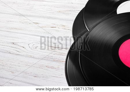 Top view of vinyl records stack over light wooden table with copy space for text