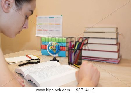 Student Young Girl working on his homework. Girl with lots of books studying for exams