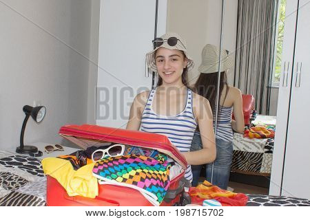 Happy young woman in colorful summer outfit sitting near the red staffed suitcase. Travel concept. Young girl packing suitcases on floor at home