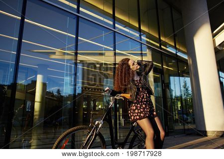 Picture of gorgeous young European female with dark bushy hair having rest outdoors in cityscape standing at glas windows building with bicycle relaxing after long bike ride. Active lifestyle