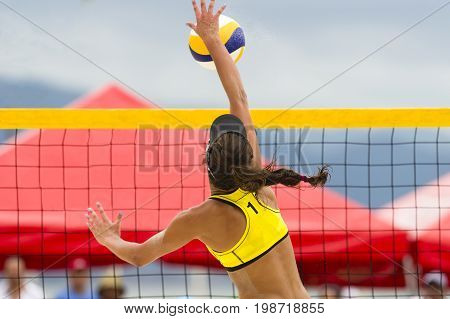 Volleyball player is a female beach volleyball player jumping at the net to spike the ball down.