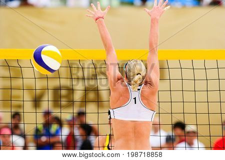 Volleyball player is a female beach volleyball player jumping up getting ready to block the ball.