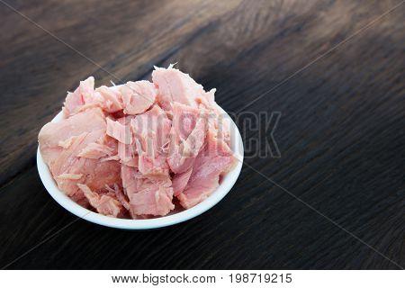 bowl of tuna chunks on wood table background. Dark tone