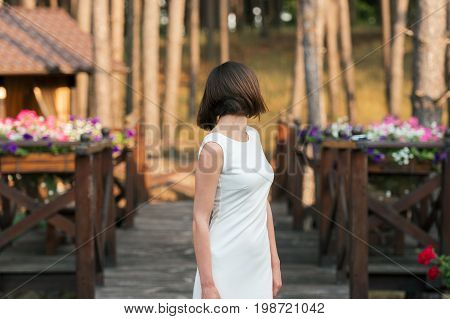 Beautiful Happy Young Woman In White Dress Dancing On Wooden Platform Near Forest Outdoors. Beautifu