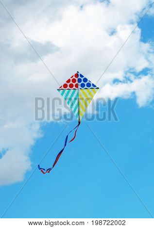 Flying kite in the blue sky against the background of clouds