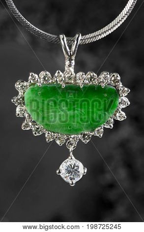 Antique green jade pendant and diamonds in white gold.