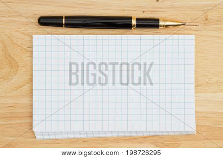 Stack of blank white graph index cards on wood desk and a pen with copy space for your message