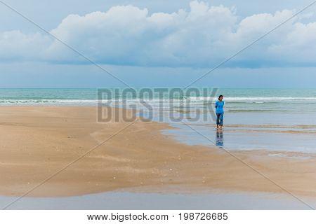 Prachuap Khiri Khan, Thailand - April  6, 2017: Asian woman (unidentified) walks along the beach in Prachuap. Weekend trips to Prachuap Khiri Khan is getting more and more popular among Thai tourists