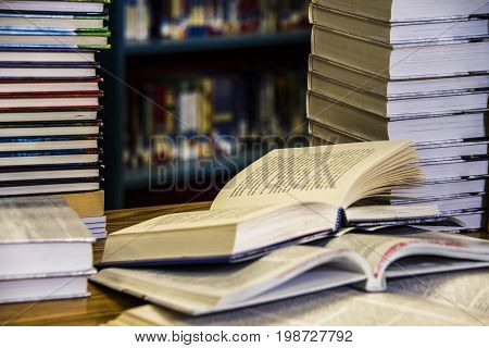 Open book, books on the table in the library, old books on table with blurry background of bookshelves, university bookstore, Stack Of Old Books in the library, Stacked Books, library concept,