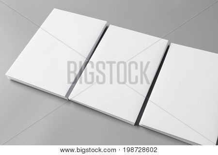 Business card, brochure magazine isolated on gray, changeable background / white paper isolated on gray