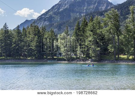 man and woman on vacation canoeing on a beautiful emerald green looking lake surrounded by green trees and large mountain ranges in the background. on a warm summer day