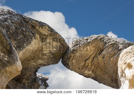 horizontal close up image of very large  tall sandstone natural formations  touching at the top with the image photographed from underneath toward the sky.